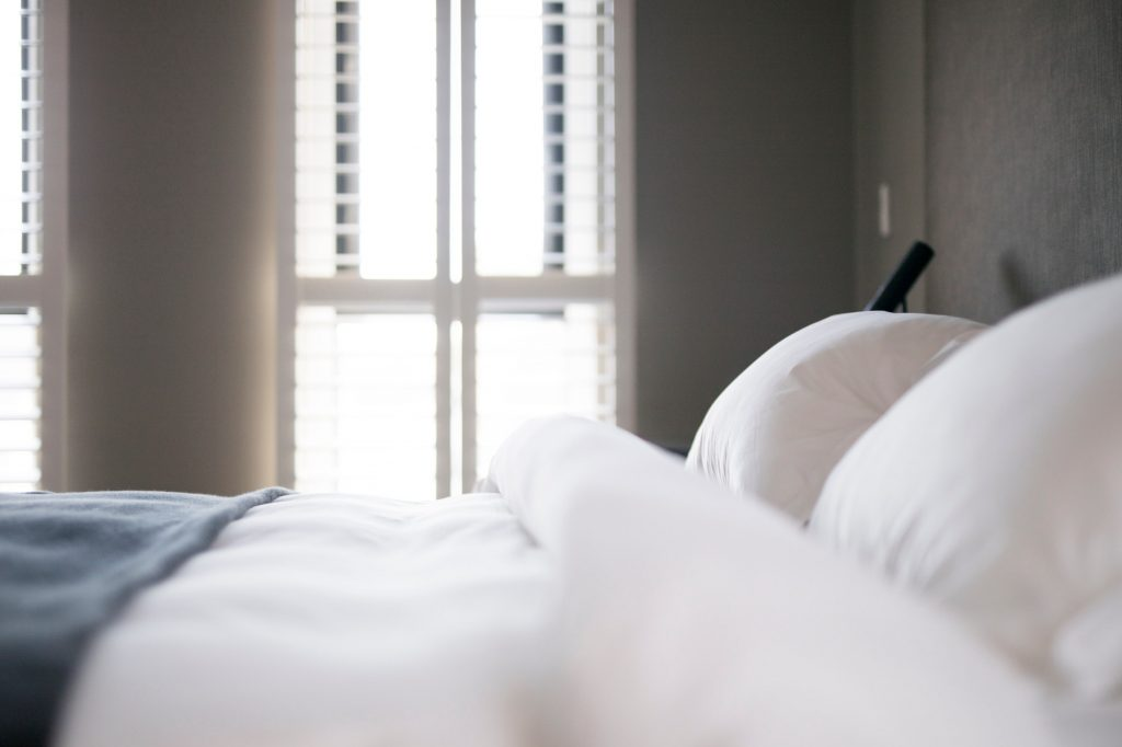 View of a hotel bedroom with a macro close up view of the bed with white crisp sheets